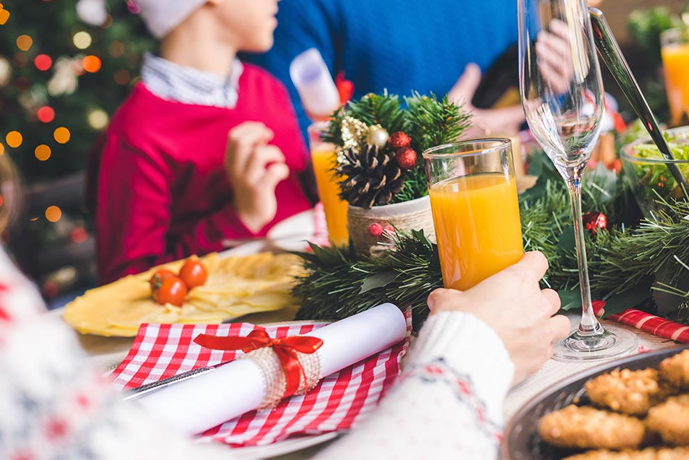 Family gathered together for Christmas dinner at a table with decorations for the holidays.