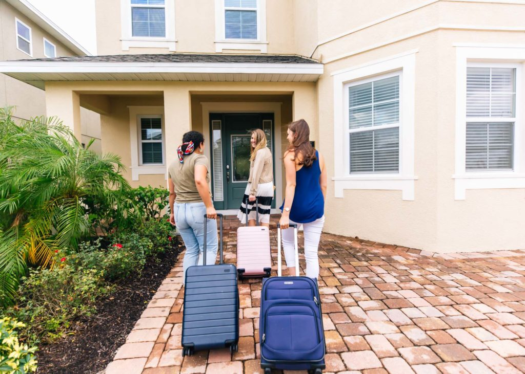 Three women happily arrive with luggage at their Encore Resort curated resort residence for a girls' getaway trip.