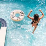 Woman jumping into a private pool at an Encore Resort vacation home rental.